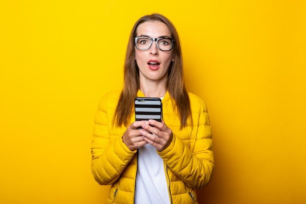 Молодая женщина в очках и желтой куртке