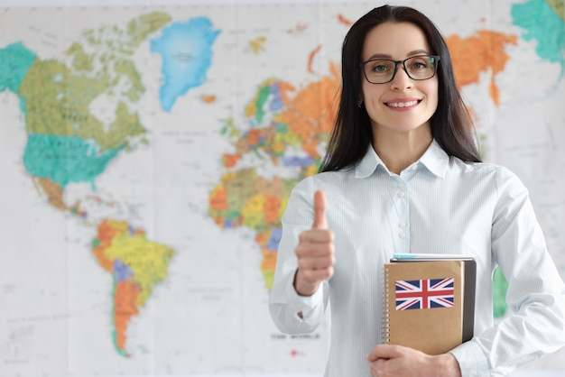 Молодая женщина в очках держит большой палец вверх и ноутбук с английским языком