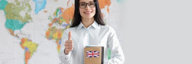 Молодая женщина в очках держит большой палец вверх и блокнот с английским языком