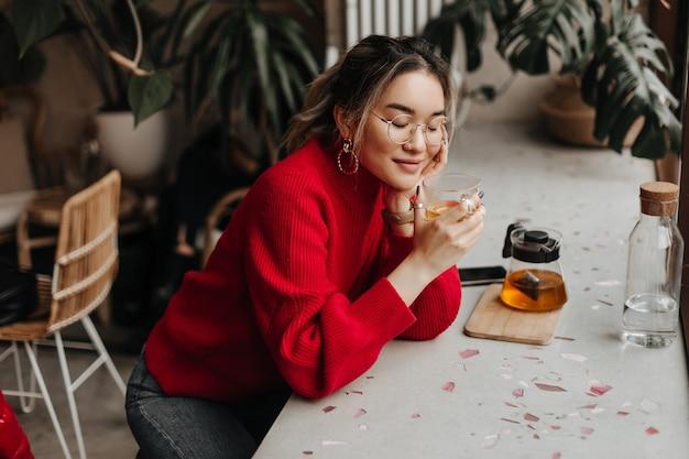 眼鏡をかけた若い女性がカフェのテーブルに寄りかかった