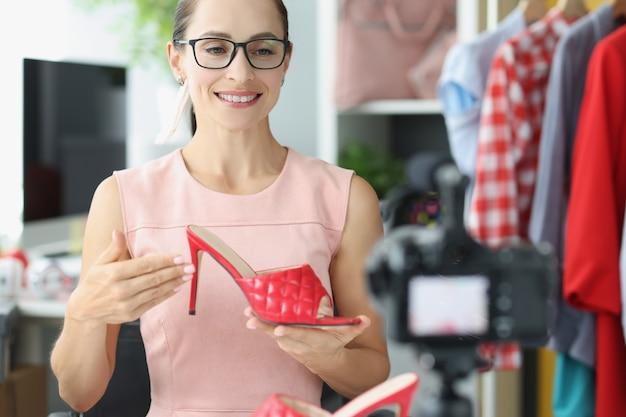 카메라 패션 블로깅 개념에 빨간 하이힐 신발을 보여주는 안경을 쓴 젊은 여성