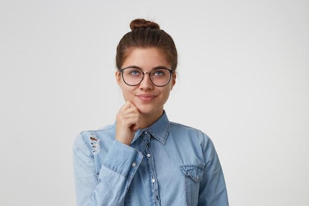 Молодая женщина в очках с темными волосами, собранными в пучок, мечтательно смотрит вверх, держа руку возле подбородка