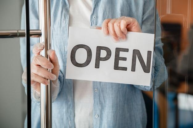 Молодая женщина в перчатках висит на входной двери кафе снова открыть знак. знак «открытое приветствие» на входной двери магазина как новая норма. прекратить изоляцию от коронавируса covid 19 для местного бизнеса.