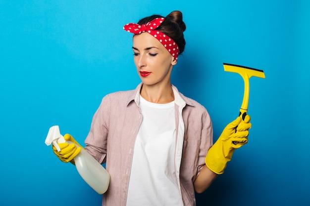 青い表面の窓を掃除するためのスプレーとスクレーパーを保持している手袋の若い女性