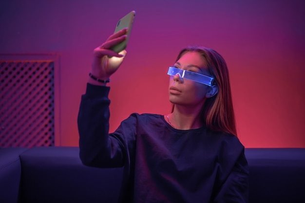 輝く眼鏡をかけた若い女性が電話を使用しています。
