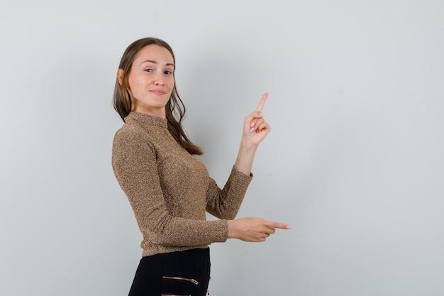Молодая женщина в золотой блузке указывая в сторону. свободное место для вашего текста