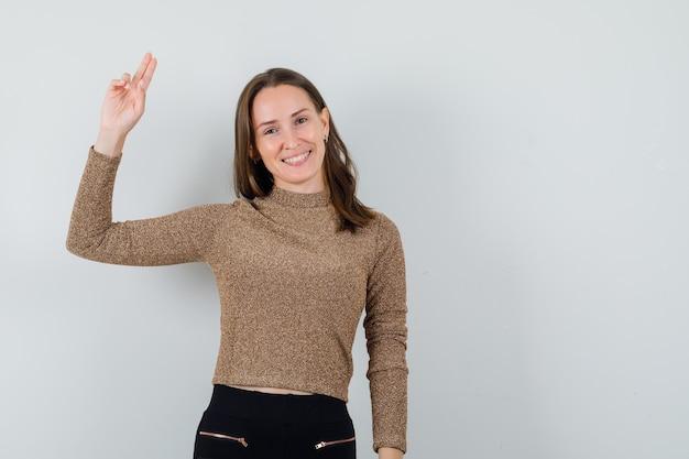 Молодая женщина в золотой блузке показывает жест прощания и выглядит позитивно, вид спереди. свободное место для вашего текста