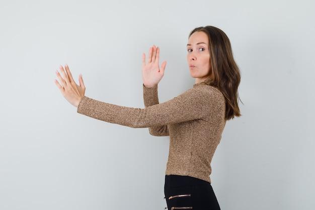 Молодая женщина в золотой блузке показывает отбивную каратэ и выглядит сосредоточенной.