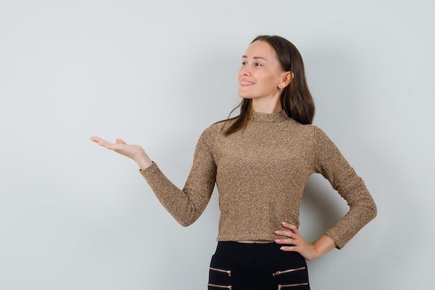 手のひらを脇に広げて陽気に見える金色のブラウスの若い女性、正面図。
