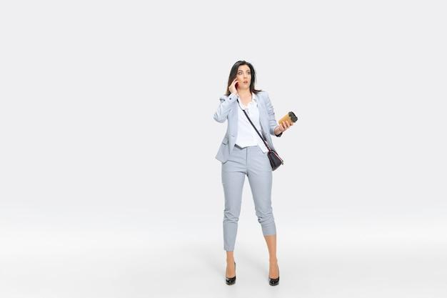 灰色のスーツを着た若い女性は、上司や同僚から衝撃的なニュースを受け取っています。コーヒーを落としながらしびれているように見えます。オフィスワーカーのトラブル、ビジネス、ストレスの概念。