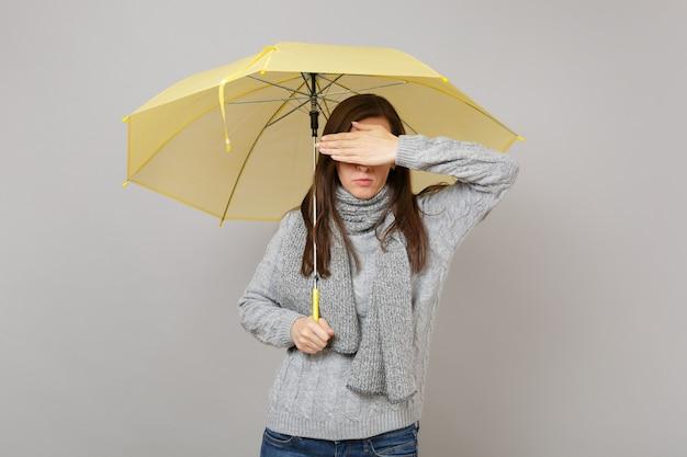 Молодая женщина в сером свитере, шарфе, закрывающем глаза рукой, держа желтый зонтик, изолированный на серой стене. концепция холодного сезона эмоций людей здорового образа жизни моды. копируйте пространство для копирования.