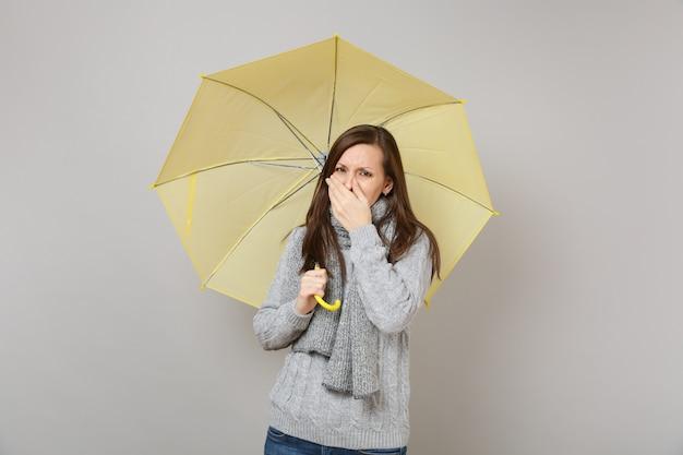 灰色のセーター、手で口を覆うスカーフ、くしゃみや咳の若い女性は、灰色の背景に分離された黄色の傘を保持します。健康的なライフスタイル、病気の病気の治療、寒い季節のコンセプト。