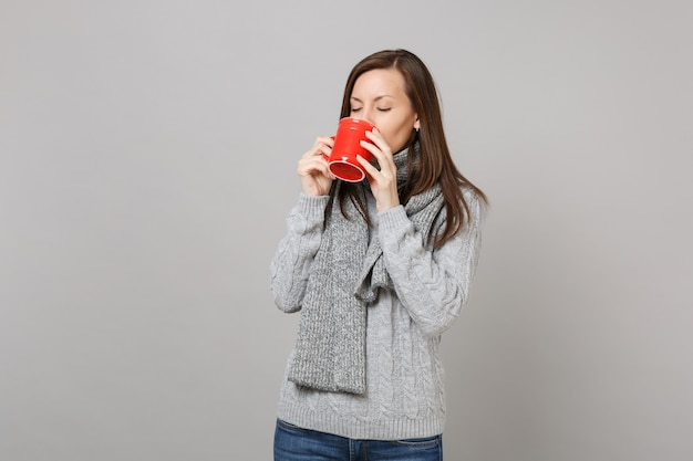 灰色のセーター、スタジオで灰色の背景に分離された赤いカップからコーヒーやお茶を飲むスカーフの若い女性。健康的なファッションライフスタイルの人々の誠実な感情の寒い季節のコンセプト。コピースペースをモックアップします。