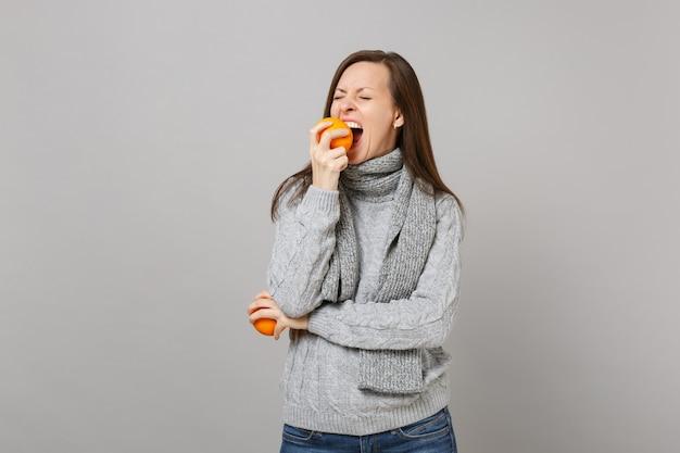 灰色のセーター、灰色の壁の背景、スタジオの肖像画に分離された噛むオレンジを保持しているスカーフの若い女性。健康的なファッションライフスタイル、人々の誠実な感情、寒い季節のコンセプト。コピースペースをモックアップします。