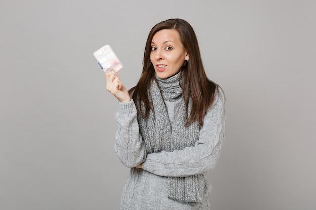 Молодая женщина в сером свитере, шарфе, держащем ежедневную коробку для таблеток, изолированную на сером стенном фоне, студийный портрет. здоровый образ жизни, лечение больных, концепция холодного сезона. копируйте пространство для копирования.