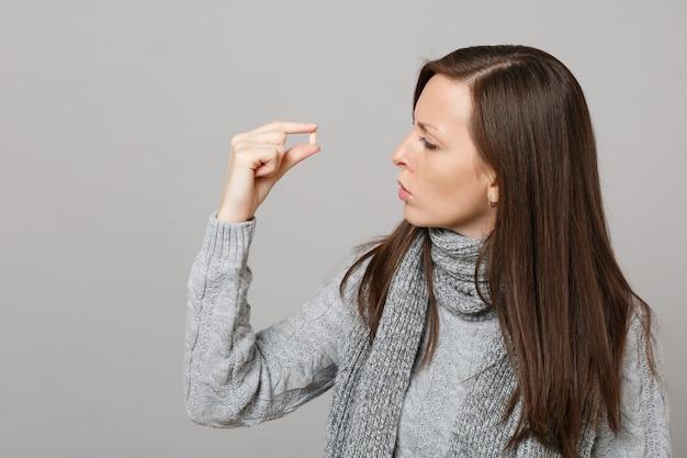 Молодая женщина в сером свитере, удерживании шарфа, глядя на таблетку лекарства, таблетку аспирина в руке, изолированную на сером фоне в студии. концепция холодного сезона лечения больных заболеваний здорового образа жизни.