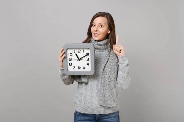 Молодая женщина в сером свитере, шарфе, указывая указательным пальцем вверх, держит квадратные часы, изолированные на сером фоне. здоровый образ жизни моды, искренние эмоции людей, концепция холодного сезона. копируйте пространство для копирования.