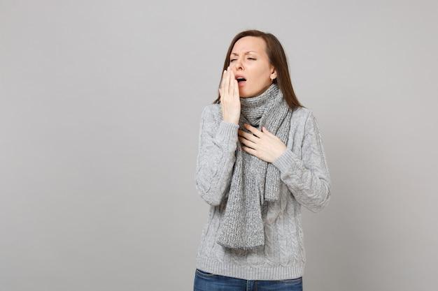 灰色の壁の背景に分離された手のひらで口を覆う灰色のセータースカーフくしゃみや咳の若い女性。健康的なライフスタイルの病気の病気の治療、風邪の季節の概念。コピースペースをモックアップします。