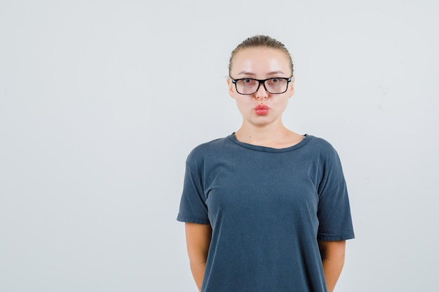 Молодая женщина в серой футболке, в очках держит губы сложенными и выглядит умно