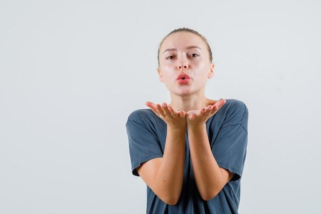 空気のキスを送信する灰色のtシャツの若い女性