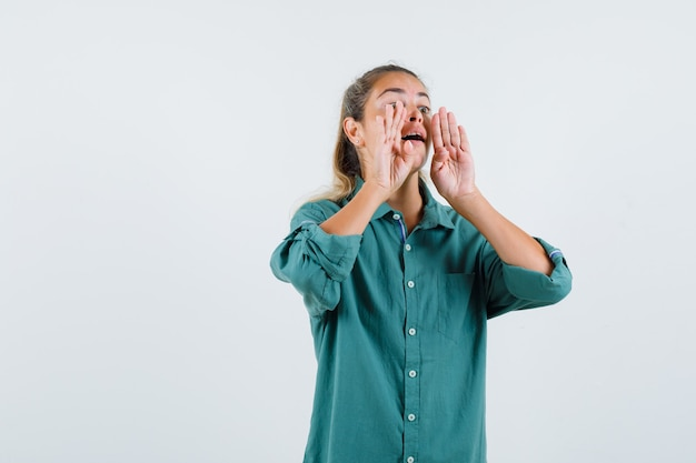 緑のブラウスを着た若い女性が誰かを呼んで集中しているように口の近くで手をつないでいる