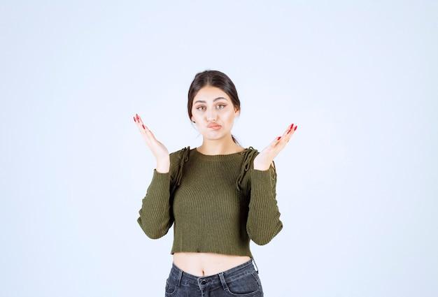 白い壁に答えを探している緑のブラウスの若い女性