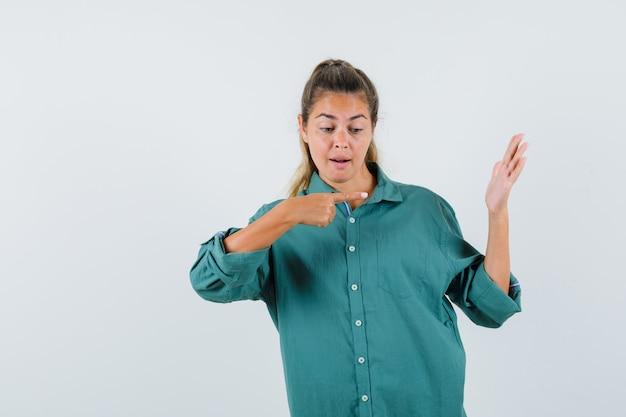 手元を指して、かわいく見える緑のブラウスの若い女性
