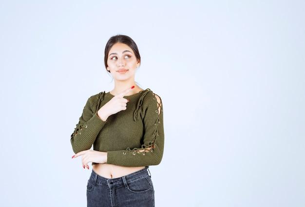 白い壁のどこかを指している緑のブラウスの若い女性