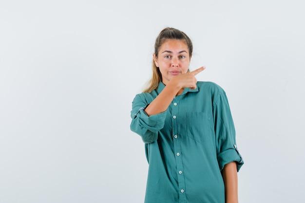 人差し指で右を指して幸せそうに見える緑のブラウスの若い女性