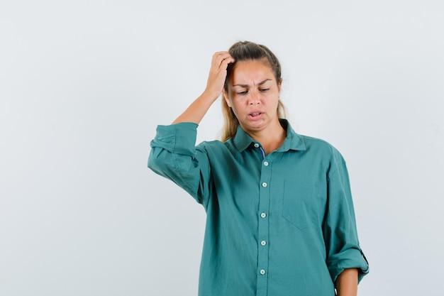 Молодая женщина в зеленой блузке почесывает голову и смотрит задумчиво