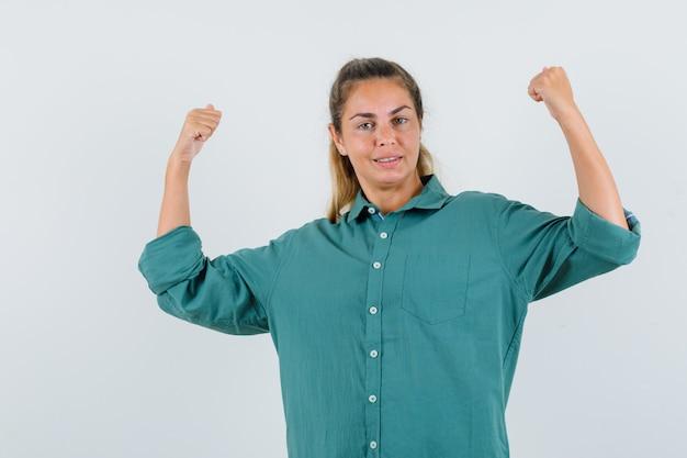 勝者のジェスチャーを示し、自信を持って見える緑のブラウスの若い女性 無料写真