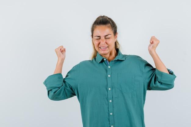 勝者のジェスチャーを示し、楽観的に見える緑のブラウスの若い女性