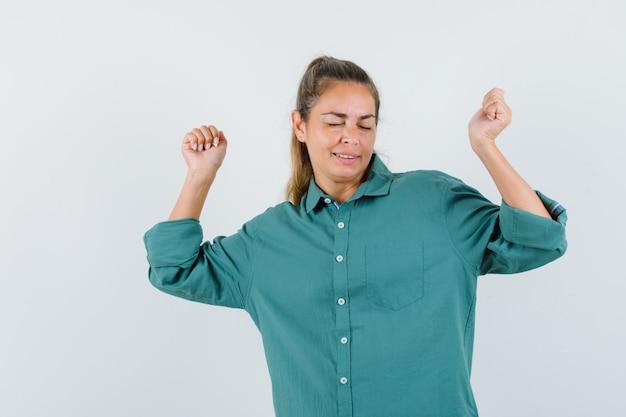 ウィンクしてかわいく見える間勝者のジェスチャーを示す緑のブラウスの若い女性