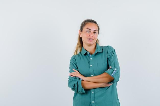 緑のブラウスの立っている腕を組んで幸せそうに見える若い女性