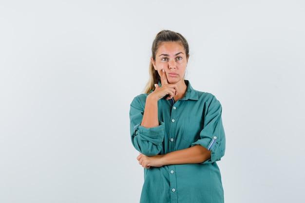 Молодая женщина в зеленой блузке стоит в позе мышления и смотрит задумчиво