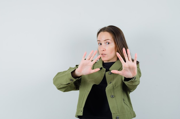 Молодая женщина в зеленой куртке, черной рубашке показывает жест стоп и выглядит обеспокоенным, вид спереди.