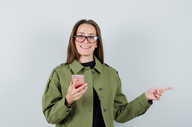 Молодая женщина в зеленой куртке, очки, указывая в сторону, держа телефон, вид спереди.