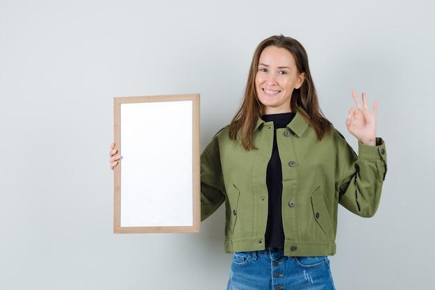 大丈夫なジェスチャーを示し、前向きに見える間、空白のフレームを保持している緑のジャケットの若い女性、正面図。