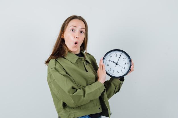 時計を保持し、驚いたように見える緑のジャケットの若い女性、正面図。