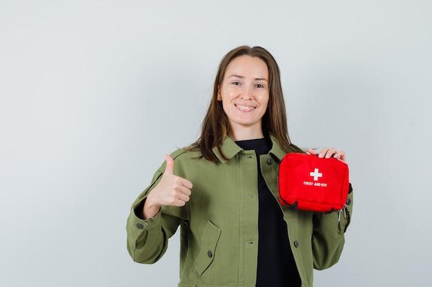 Молодая женщина в зеленой куртке, держащей аптечку, показывая большой палец вверх и выглядя довольным, вид спереди.