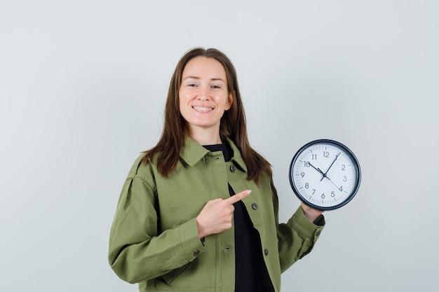 緑のジャケットを着た若い女性が時計を指して幸せそうに見える、正面図。