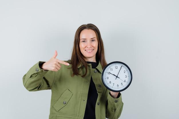 緑のジャケットを着た若い女性が時計を指して、陽気に見える、正面図。
