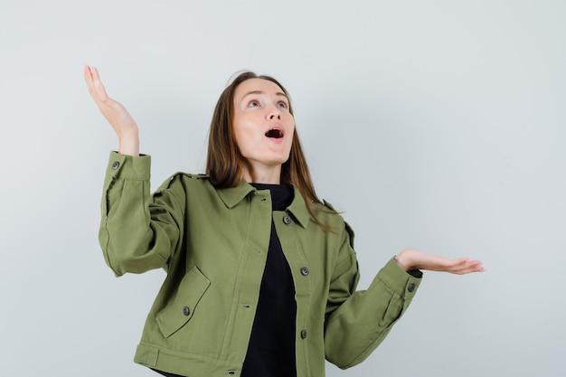 緑のジャケットを着た若い女性が疑わしい方法で手を上げて、混乱しているように見える、正面図。