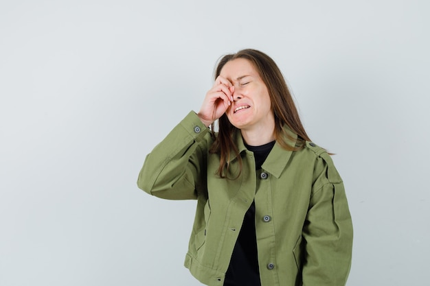 Молодая женщина в зеленой куртке, протирая глаз, плача и грустно, вид спереди.