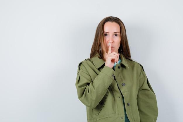 沈黙のジェスチャーを示し、注意深く見ている緑のジャケットの若い女性、正面図。