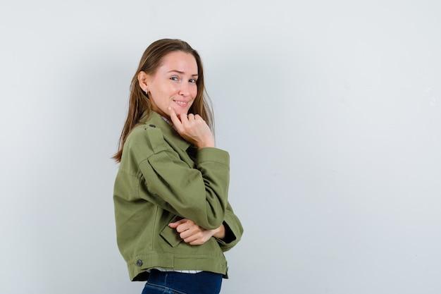 思考ポーズで立ってエレガントに見える緑のジャケットの若い女性。