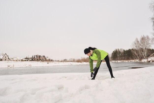 Молодая женщина в зеленой куртке стоит на зимнем озере и наклоняется во время разминки