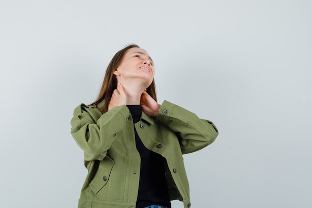 목 통증으로 고통 받고 불편한 전면보기를 찾고 녹색 재킷에 젊은 여자.