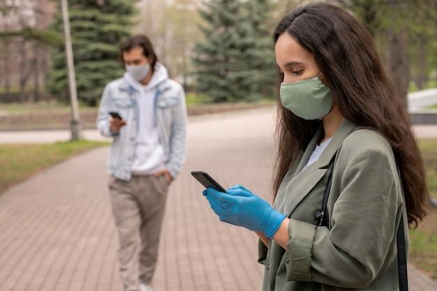 緑のマスクと手袋をはめて都市公園に立っている若い女性とスマートフォンでsmsにテキストメッセージを送信、コロナウイルスの概念の間に社会的な距離