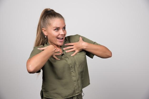 Молодая женщина в зеленой одежде смеется.